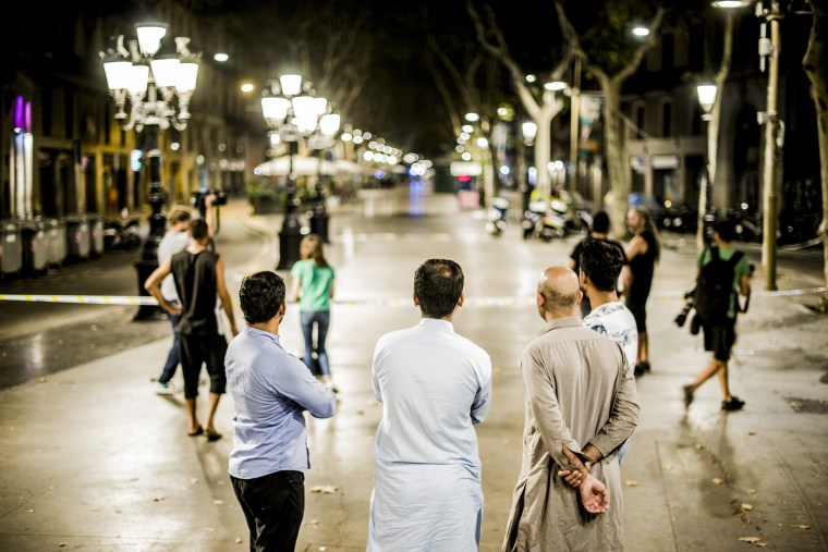 Image: Pakistani Muslim men watch as police work at the scene of a terrorist attack in Barcelona, Aug. 17, 2017.
