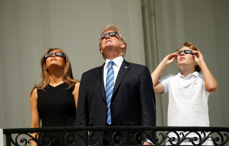 Image: U.S. President Trump watches the solar eclipse with first Lady Melania Trump and son Barron from the Truman Balcony at the White House in Washington