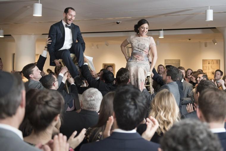 Kantzer and Hoffman enjoy traditional Jewish festiviites at their wedding.