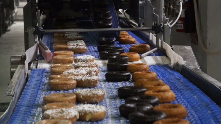 Donuts travel along the conveyor belt to be glazed, frosted and sprinkled!