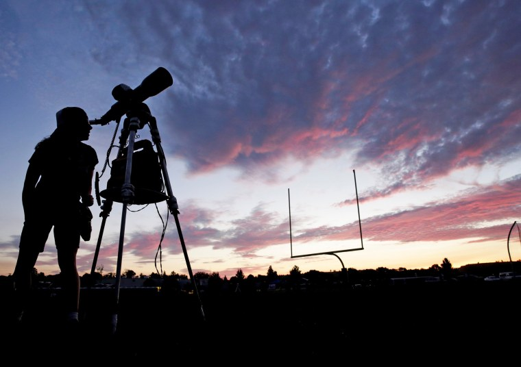 Image: A woman looks through a telescope on the football field at Madras High School the evening before a solar eclipse in Madras, Oregon