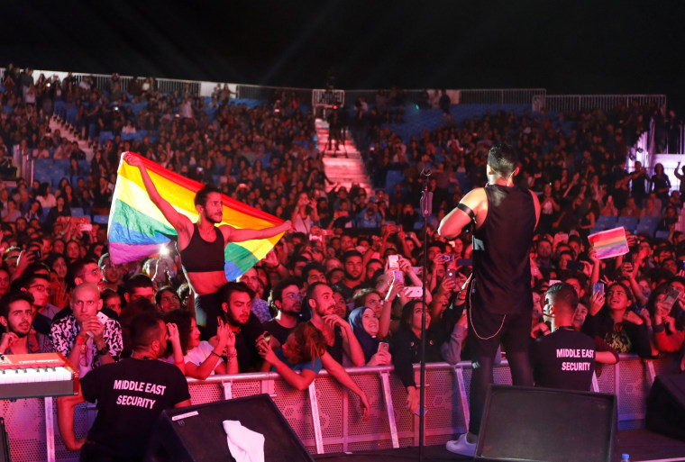 Image: A fan of Lebanese alternative rock band Mashrou' Leila holds a rainbow flag during their concert at the Ehdeniyat International Festival in Ehden town
