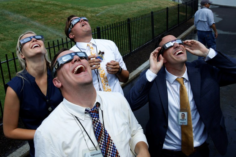 Image: Members of the media watch the solar eclipse at the White House in Washington
