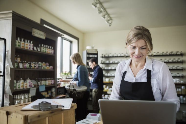 Apothecary shop owner working at laptop
