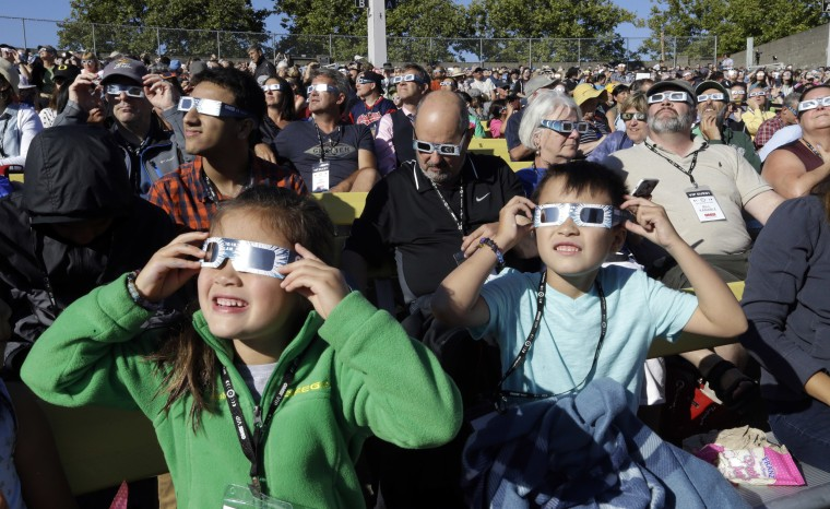 Image: A crowd wears protective glasses as they watch the beginning of the solar eclipse from Salem, Oregon