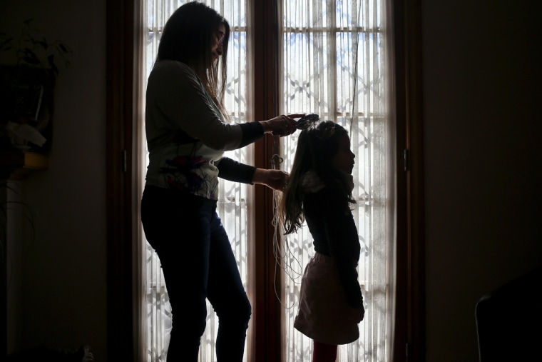 Image: Monica Flores combs her daughter's hair at their home