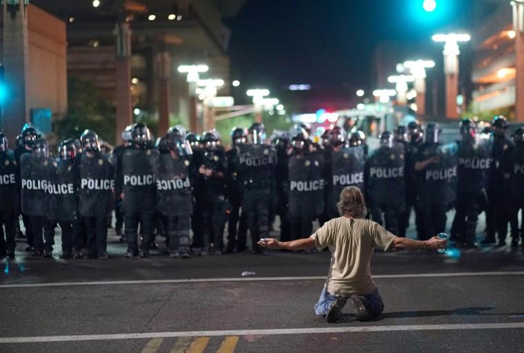 Image: A demonstrator taunts police while Trump speaks in Phoenix, Arizona.