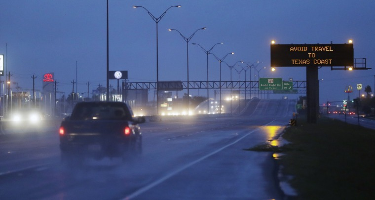Image: Motorists pass a warning sign as Hurricane Harvey approaches the Gulf Coast area