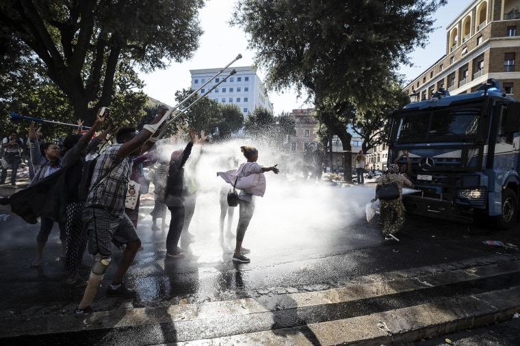 Image: Italian law enforcement officers use water cannons to disperse migrants in Rome