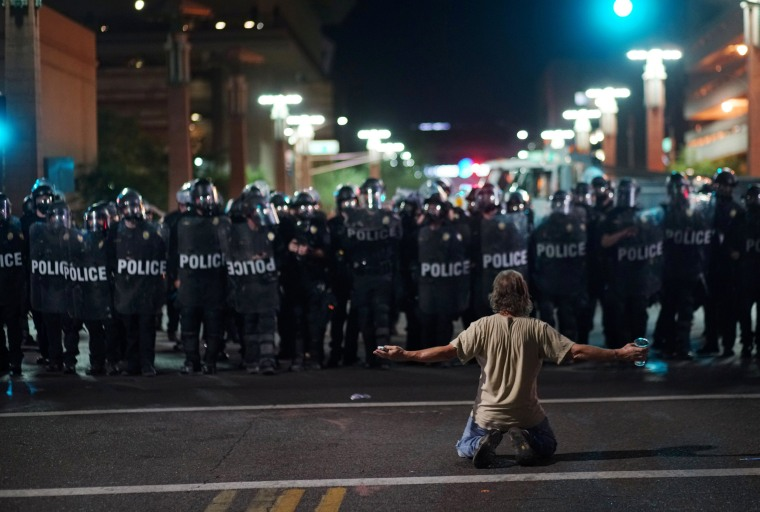 Image: A demonstrator taunts Police officials after a Donald Trump campaign rally in Phoenix