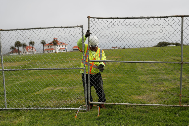 Image: A worker installs a fence at Crissy Field in anticipation of Saturday's Patriot Prayer rally and counter demonstration in San Francisco, California