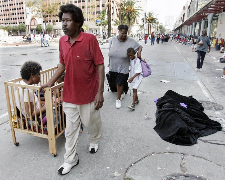 Image: A family of Hurricane Katrina victims walk past a covered body in front of the convention center in New Orleans