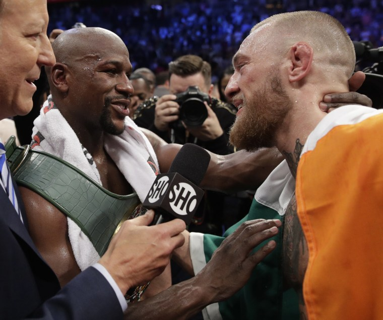 Floyd Mayweather Jr., left, speaks with Conor McGregor after a super welterweight boxing match Saturday, Aug. 26, 2017, in Las Vegas.