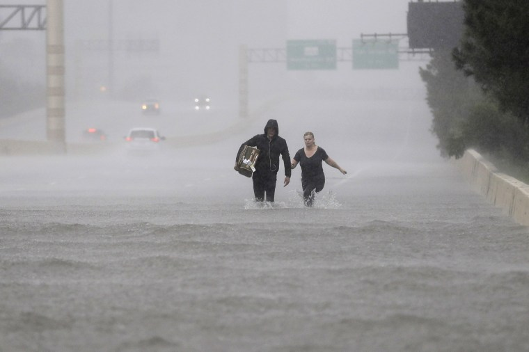 Image: Two people walk down a flooded section of Interstate 610 in floodwaters