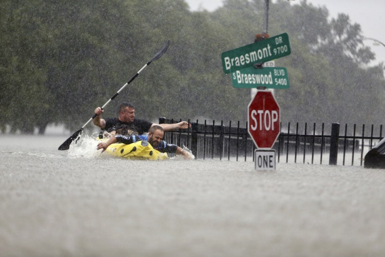 Image: Two kayakers try to beat the current pushing them down an overflowing Brays Bayou along S. Braeswood in Houston