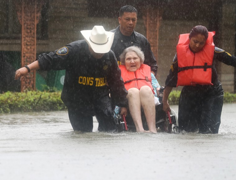 Image: Precinct 6 Deputy Constables Sgt. Paul Fernandez, from left, Sgt. Michael Tran and Sgt. Radha Patel rescue an elderly woman
