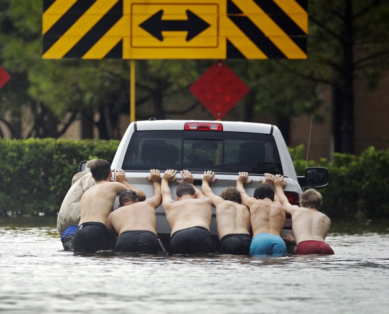 Image: People push a stalled pickup to through a flooded street in Houston