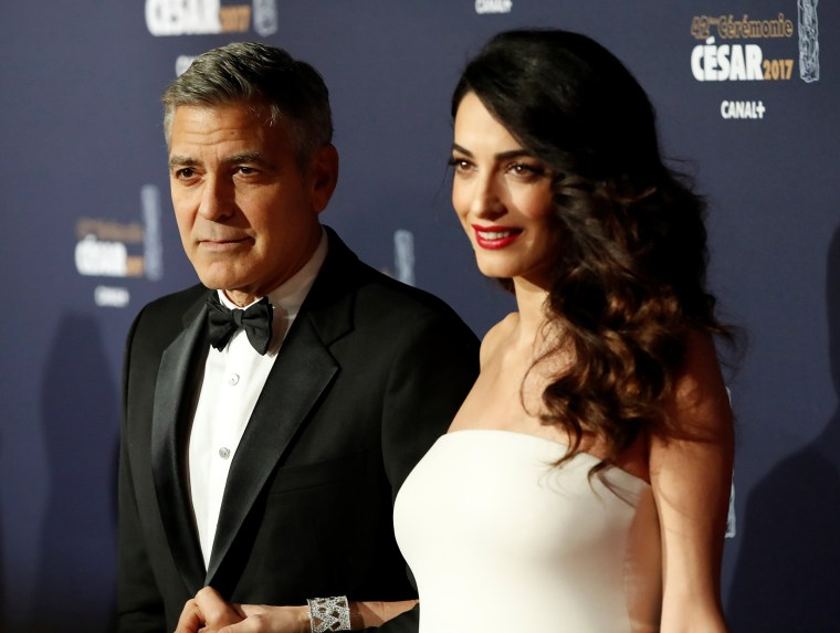 Image: FILE PHOTO: Clooney and his wife Amal pose as they arrive at the 42nd Cesar Awards ceremony in Paris