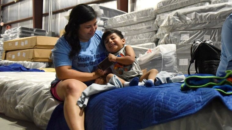 Lopez plays with her son in the warehouse at Gallery Furniture in Houston