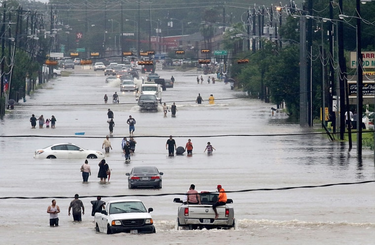 Image: People walk through the flooded waters of Telephone Rd. in Houston