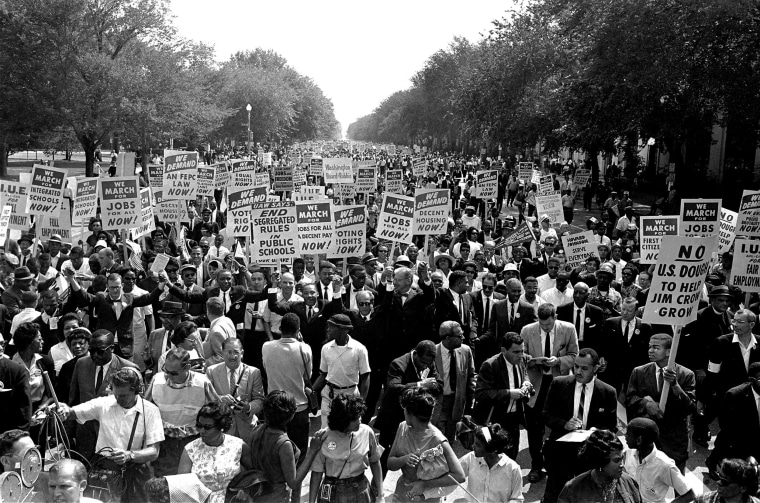 Image: Dr. Martin Luther King Jr., center left with arms raised, marches along Constitution Avenue with other civil rights protesters carrying placards, from the Washington Monument to the Lincoln Memorial during the March on Washington, Aug. 28, 1963.