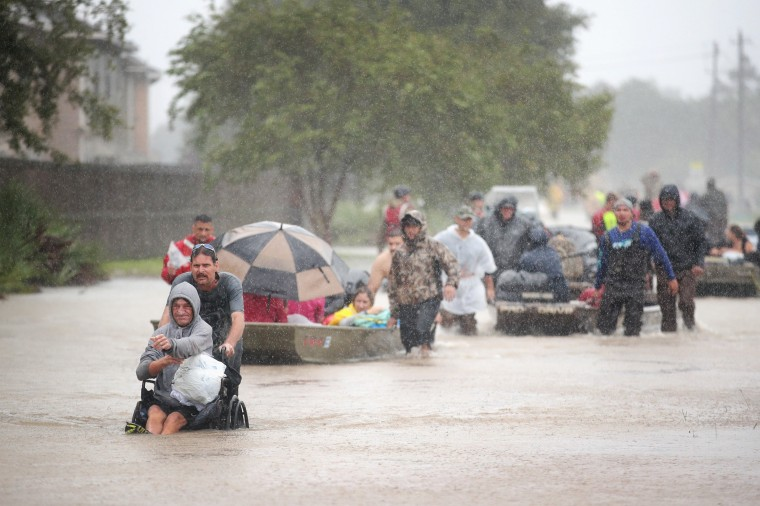 Image: People are rescued from a flooded neighborhood in Houston