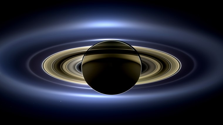 Image: On July 19, 2013, NASA's Cassini spacecraft slipped into Saturn's shadow and turned to image the planet, seven of its moons, its inner rings, and, in the background, our home planet, Earth.