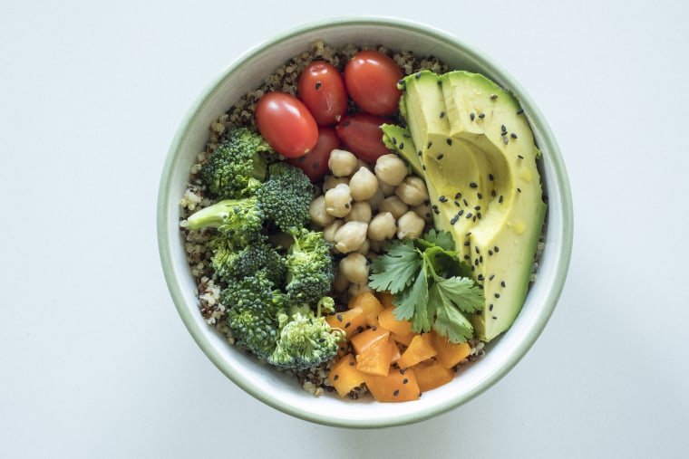 Image: A bowl of quinoa with avocado, cherry tomatoes, broccoli, orange peppers, chickpeas and cilantro.