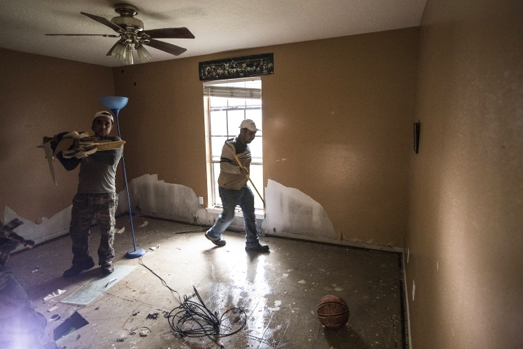 Image: A construction crew cleans out the home of Kenny Licona, which was flooded out from Tropical Storm Harvey