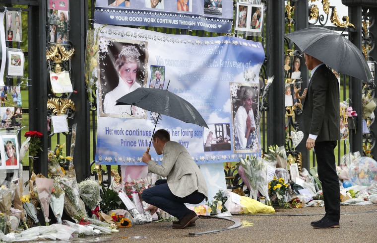 Image: Britain's Prince William, right, and Prince Harry look at floral and pictorial tributes to their late mother Princess Diana placed on the gates of Kensington Palace, London