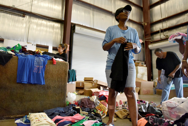 Image: Evacuee Jackson sorts through donated clothing in Houston