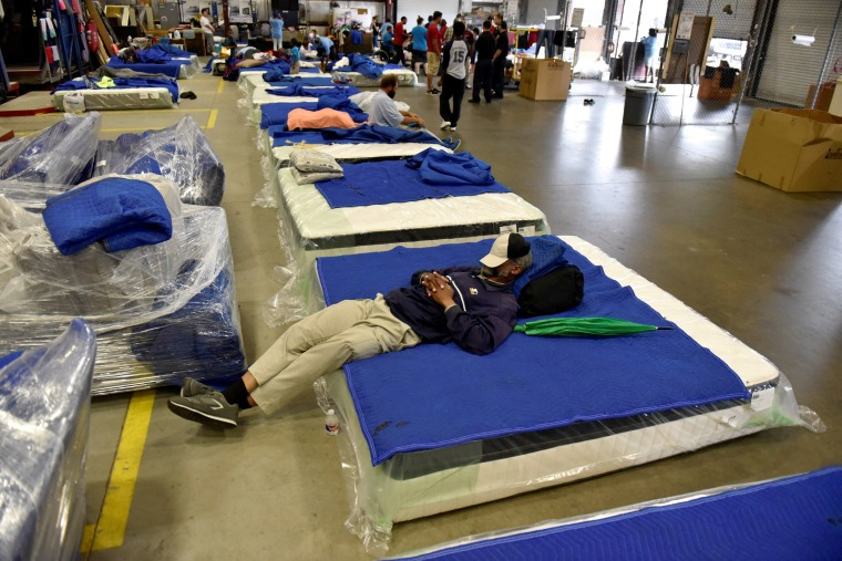 Image: Evacuees get some rest in the warehouse at Gallery Furniture in Houston