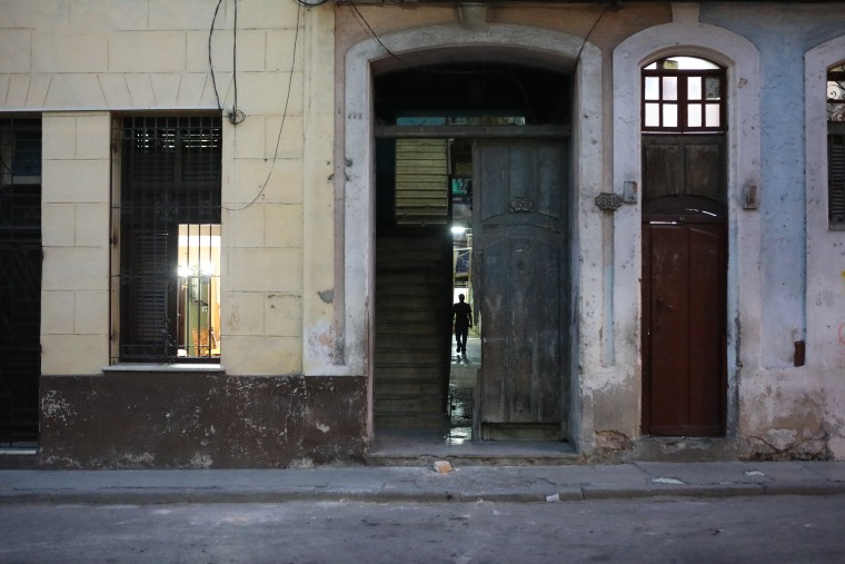 Image: A man walks into his residence during the evening hours in Matanzas, Cuba