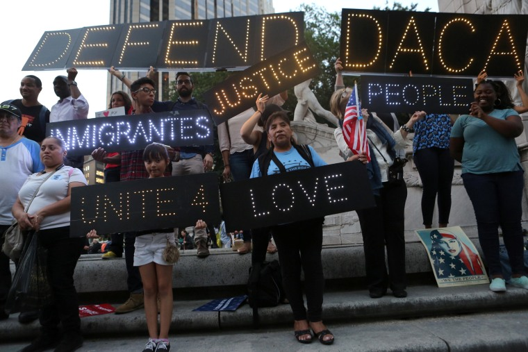 Image: People hold signs against U.S. President Donald Trump's proposed end of the DACA program that protects immigrant children from deportation at a protest in New York City
