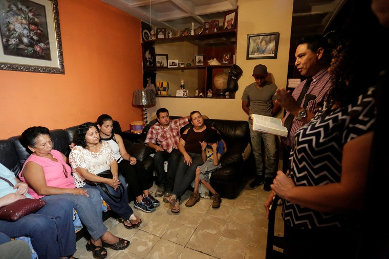 Image: Evangelical preacher talks to relatives of the Saldivar family, whose van was reportedly carrying six family members when it was swept away by floodwaters from Hurricane Harvey, at their house in Monterrey