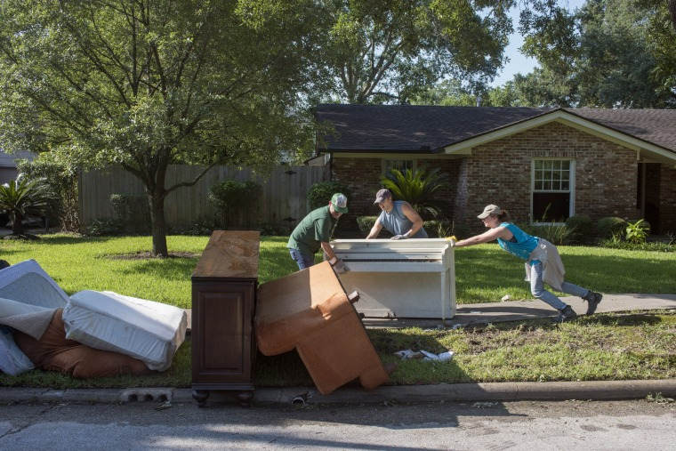 Image: Friends band together to help Scott Hausman-Weiss remove damp sheet-rock, waterlogged floors, and ruined possessions from his home on Braesvalley Drive, Houston, after it flooded during Hurricane Harvey.
