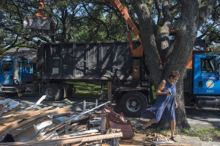 Image: Amy Shannon, 60, watches her waterlogged possessions, and the interior of her house on Braeswood Drive, as it's loaded into a dump truck, after it was flooded during Hurricane Harvey.