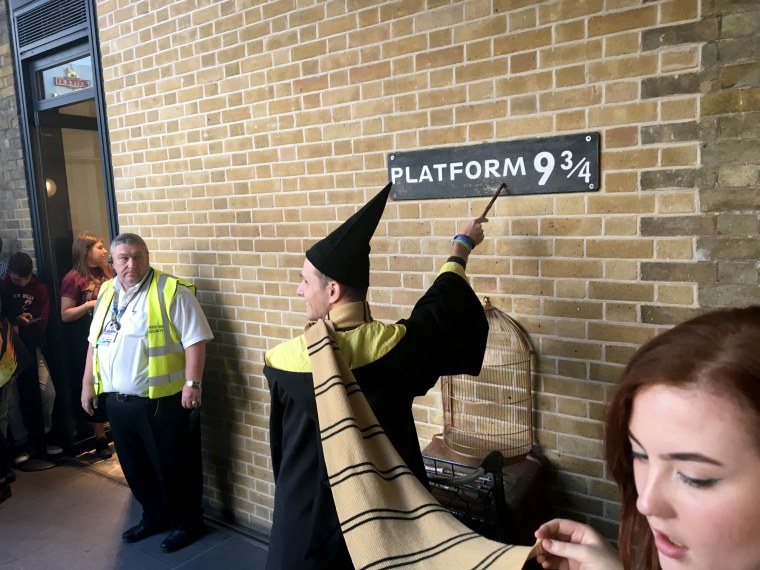 Image: Fans lined up to pose with the Platform 9  3/4  sign.