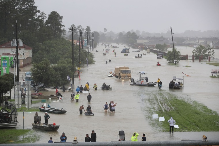 Image: People walk down a flooded street as they evacuate their homes from flooding caused by Hurricane Harvey