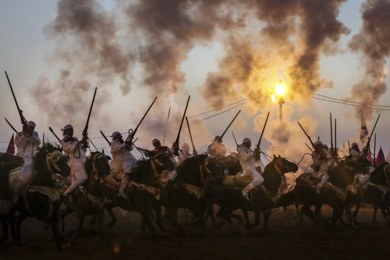 Image: Horse riders fire their gunpowder filled rifles as they take part in Tabourida