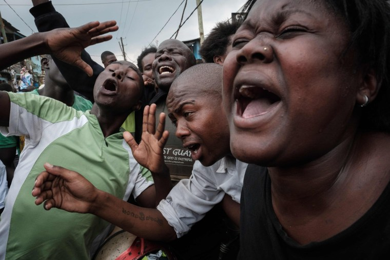Image: Supporters of Kenya's opposition party joke as they pretend to cry for Kenyan President Uhuru Kenyatta
