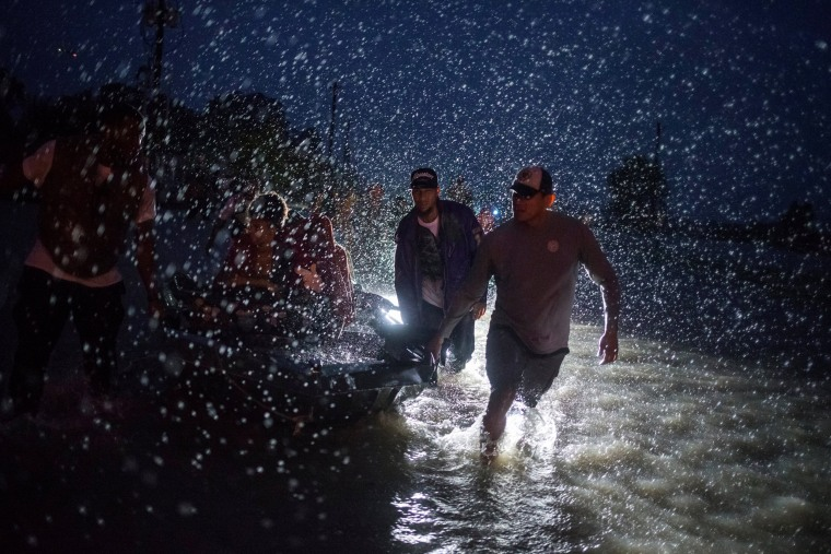 Image: Samaritans help push a boat with evacuees to high ground during a rain storm caused by Tropical Storm Harvey along Tidwell Road in east Houston