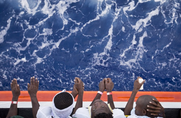 Image: African migrants stand on the deck of a rescue vessel in the Mediterranean Sea