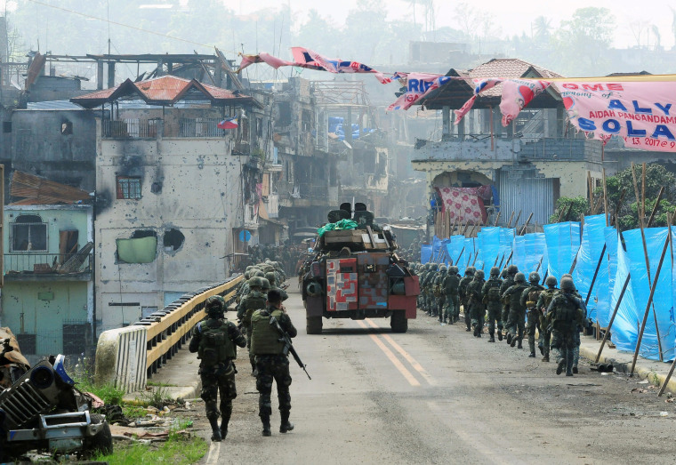 Image: Government troops march towards the Mapandi bridge during a battle against insurgents