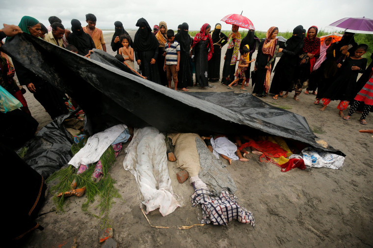 Image: People cover the bodies of Rohingya refugee women and children who died after their boat capsized while crossing the border through the Bay of Bengal, at Shah Porir Dwip, near Teknaf