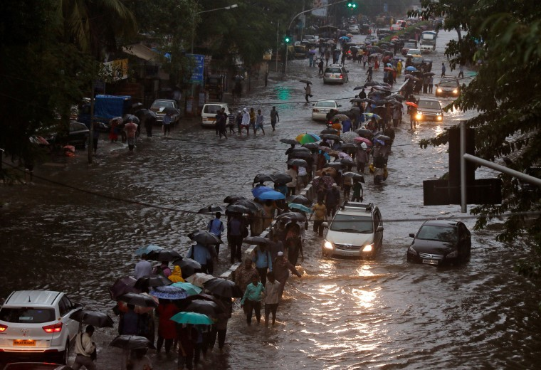 Image: Commuters walk through water-logged roads after rains in Mumbai