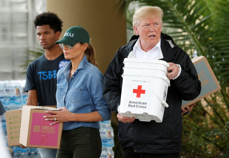 Image: U.S. President Donald Trump and first lady Melania Trump help volunteers deliver supplies to residents at a relief supply drive-thru during a visit with flood survivors and volunteers in the aftermath of Hurricane Harvey in Houston