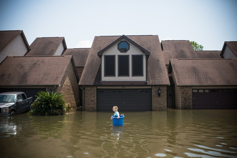 Image: Jenna Fountain carries a bucket down Regency Drive to try to recover items from their flooded home