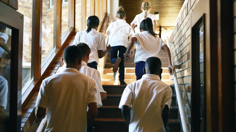 Young students running up stairs at the school