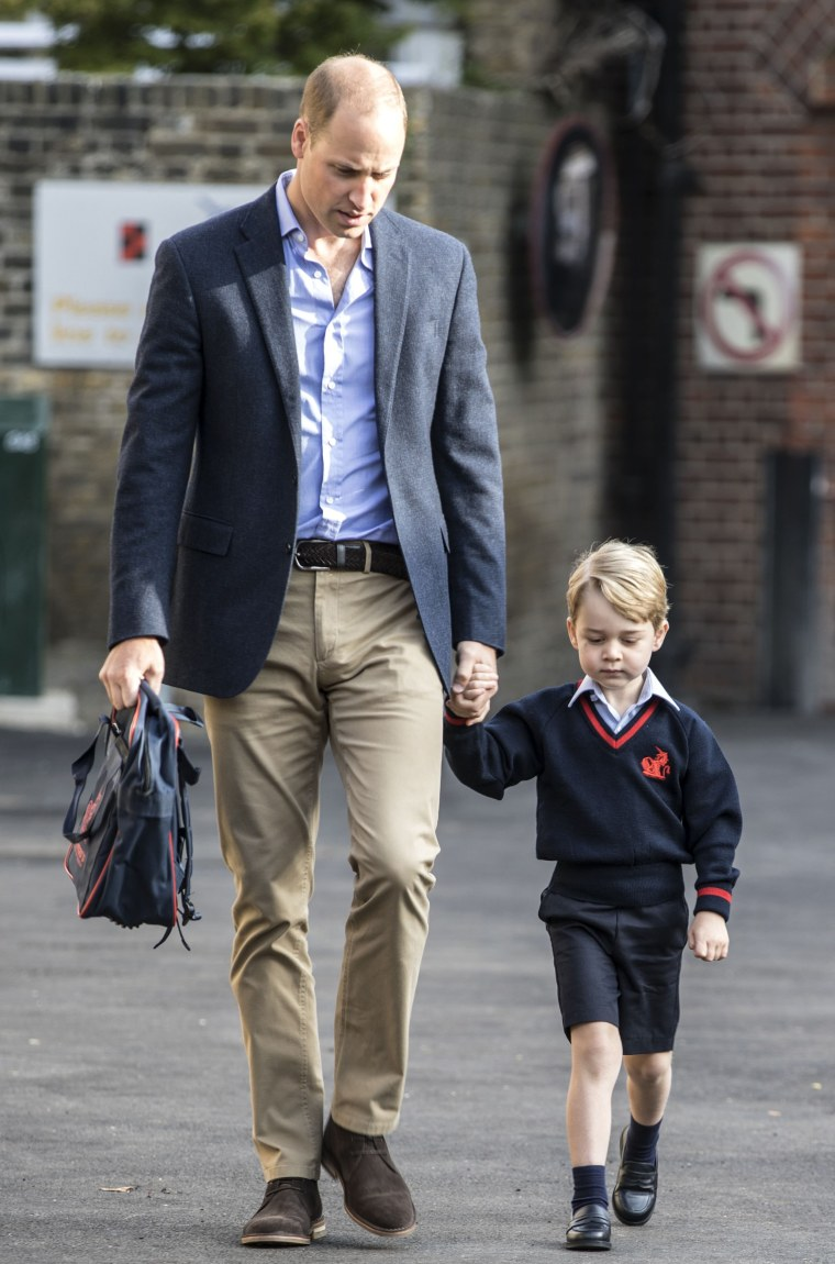Britain's Prince George accompanied by Britain's Prince William (L), Duke of Cambridge arrives for his first day of school.